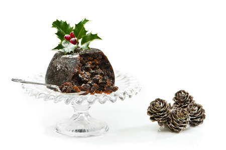 plum pudding: Serving of Christmas pudding with festive decoration on white background