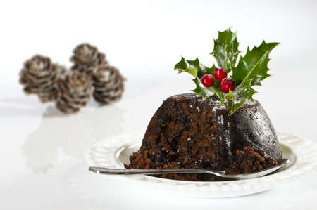 plum pudding: Serving Christmas pudding on white background