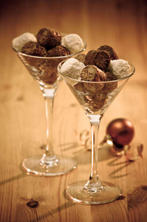 fine wood: Chocolate truffles in glasses on wooden table with Christmas bauble Stock Photo