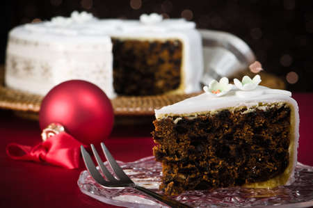 Slice of Christmas cake with dessert fork, remainder of cake  in festive background  Stock Photo - 5972923