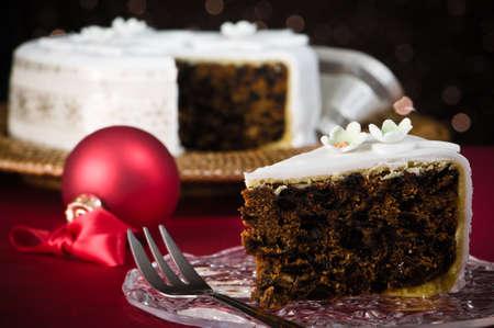 christmas cake: Slice of Christmas cake with dessert fork, remainder of cake  in festive background  Stock Photo