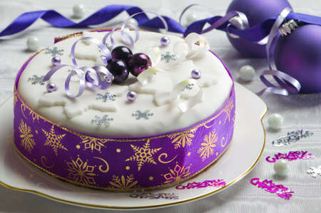 Festive Christmas cake with purple theme decorated with baubles, snowflakes and streamers photo