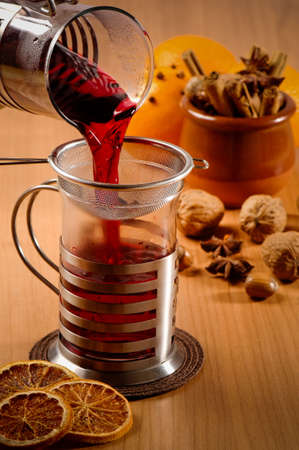 Glass of mulled wine being poured from jug with nuts and spices in background photo