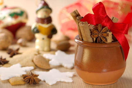 Festive seasonal nuts and spices with Christmas decorations in background photo
