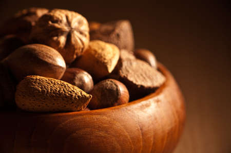 Nut selection in wooden bowl with shallow depth of field and focus on front almond in shell photo