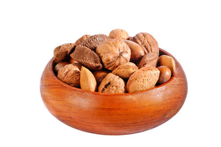 Selection of whole nuts in wooden bowl isolated on white background photo