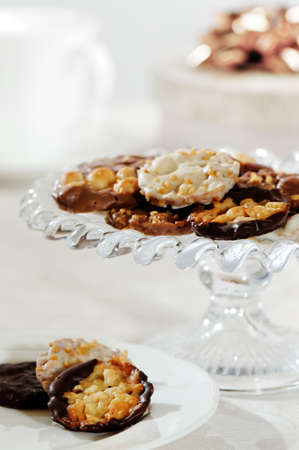Florentine biscuits on glass comport and plate with gift in background  photo