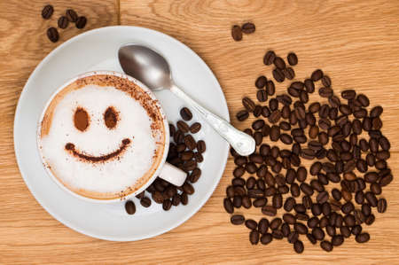 Cappuccino coffee with smiley face on wooden table, overhead view photo