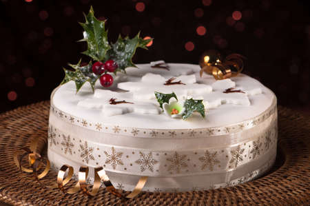 christmas cake: Christmas fruit cake decorated with holly and berries with sparkly background Stock Photo