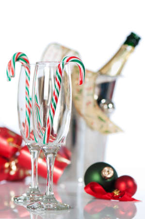 Christmas champagne glasses with candy canes and bottle in ice bucket in background photo