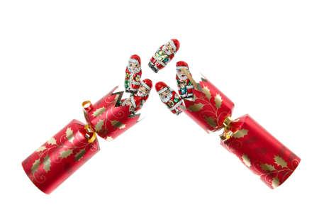 galletas integrales: Christmas cracker separado con papel de aluminio cubierto de chocolate Santas volando fuera  Foto de archivo