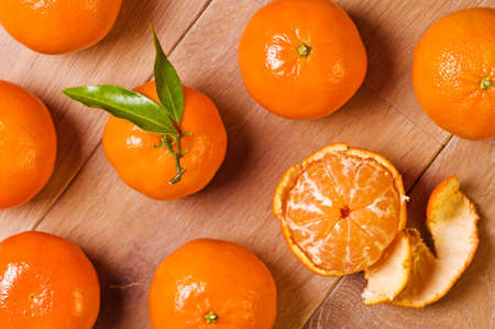 soyulmuş: Overhead view of clementine fruits, one with leaves and one half peeled