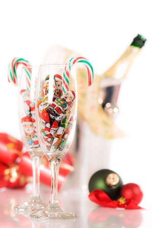 Festive holiday celebration with bottle of champagne on ice with glasses filled with candy canes and chocolate santas photo