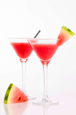 Watermelon drinks in glasses with wedge of melon garnish on white background