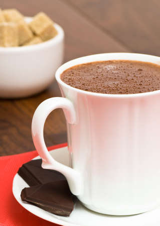chocolaty: Mug of hot chocolate drink with brown sugar cubes in background
