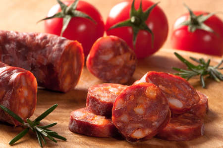 chorizo: Chorizo sausage slices with rosemary herbs and tomatoes in background