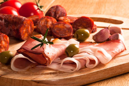 Spanish chorizo sausage with parma ham and olives garnished with rosemary herbs photo