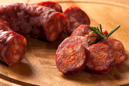 chorizo: Spanish chorizo sausage with rosemary on rustic board