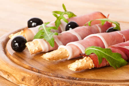 Bread sticks wrapped with parma ham with rocket salad and black olives photo