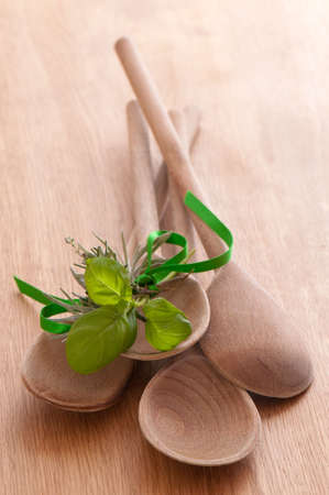 sprigs: Rustic wooden spoons on pine table with bundle of tied herbs Stock Photo
