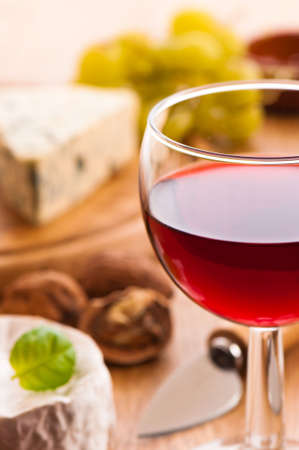 Wine with cheese selection in background - focus on rim of glass - shallow depth of field photo