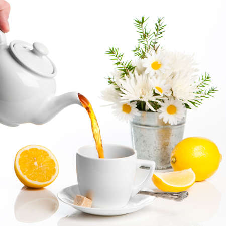 Pouring lemon tea from white teapot with vase of flowers in background photo