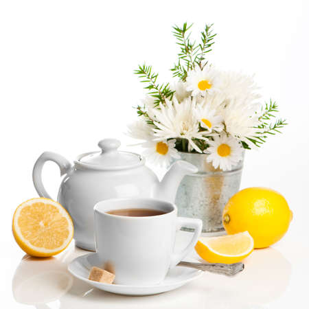 Cup of refreshing lemon tea with teapot on white background with vase of spring flowers in background photo