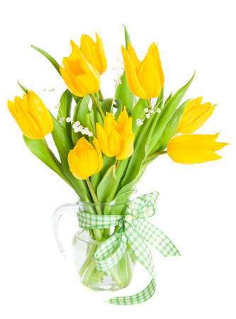 Glass vase of yellow tulips with jewels, tied with green bow photo