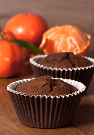 Chocolate orange muffins with peeled orange in background on rustic table photo