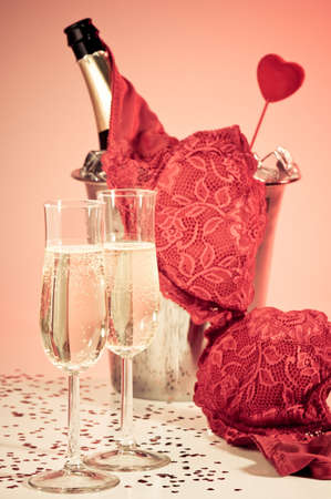 saint valentines: Valentine seduction with champagne and lacy bra over ice bucket containing vintage champagne