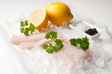 Fresh cod fillets of fish over crushed ice with parsley and lemon with salt and peppercorns photo