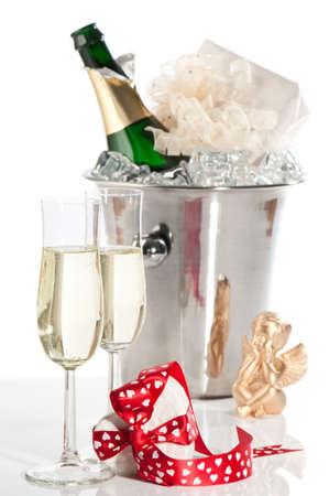 Valentine champagne with gift wrapped with heart bow, cherub and ice bucket in background photo