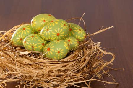 nestled: Painted Easter eggs nestled in straw lined nest