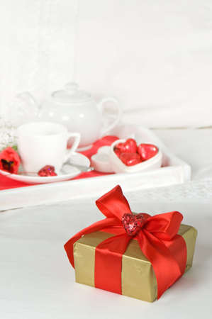 Breakfast in bed for a special occasion with gift wrapped in red ribbon photo