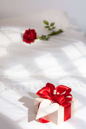Valentines gift on bed in morning sunlight with rose on pillow photo
