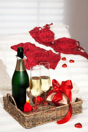 Champagne breakfast with heart shaped chocolates and gift with lacy lingerie on pillow photo