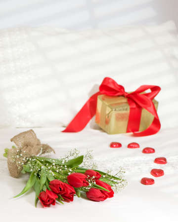 Bunch of bright red tulips on sunlit bed with gift wrapped with red ribbon and heart shaped chocolates Stock Photo - 6303956