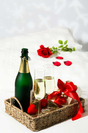 trays: Champagne breakfast in bed with single red rose on pillow and gift wrapped in red ribbon Stock Photo
