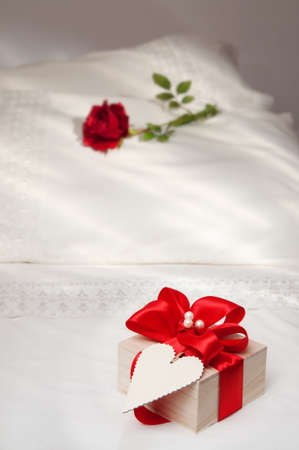 Gift on bed with red rose on pillow for Valentines day photo