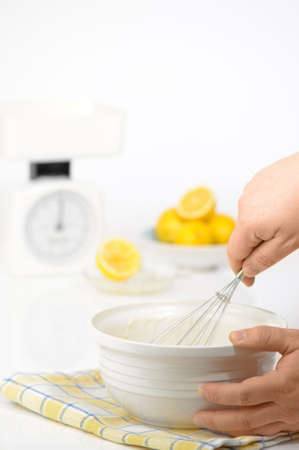shrove: Whisking pancake batter in preparation for Shrove tuesday with weighing scales and lemons in background
