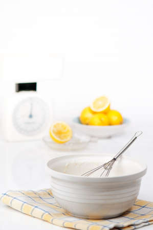 hotcakes: Pancake batter in bowl with metal whisk with measuring scales and lemons in background
