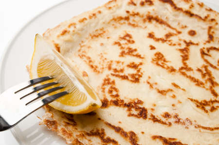 shrove tuesday: Section of freshly made pancake sprinkled with sugar with lemon wedge on fork