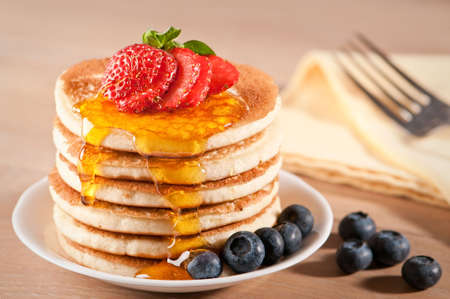 Plate of pancakes dripping with maple syrup with strawberry and blueberries
