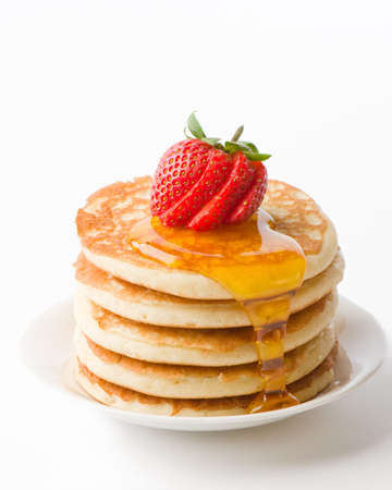 hotcakes: Plate of pancakes with maple syrup topped with sliced strawberry Stock Photo