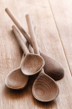 Old rustic wooden spoons laid together on table top photo