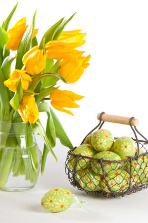 Basket of painted Easter eggs with vase of spring tulips