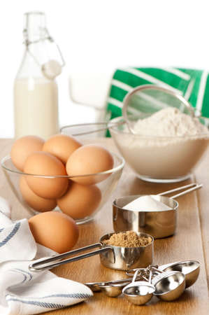 jugs: Ingredients for baking on table top with apron thrown over back of chair in background Stock Photo