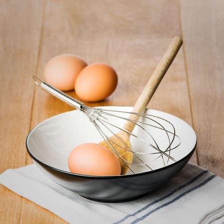 kitchen utensils: Equipos para hornear con la mezcla de la taza, la cuchara de madera y el batidor