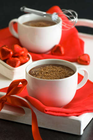 Chocolate desserts on bright red napkins with chocolate heart decorations photo