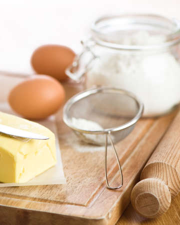 sifter: Baking ingredients with flour, eggs and butter on rustic board, selective focus on butter knife